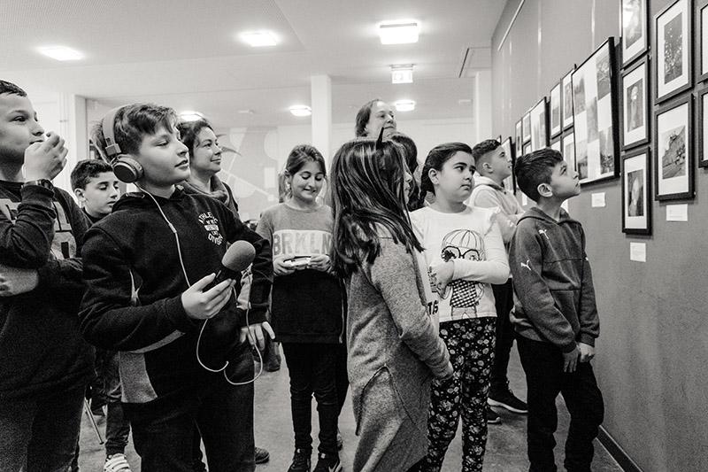 Kinder betrachten Fotos an Wand