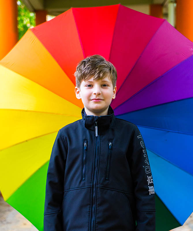 Junge vor buntem Regenschirm