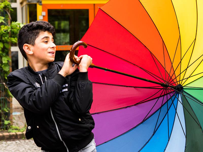 Junge mit buntem Regenschirn