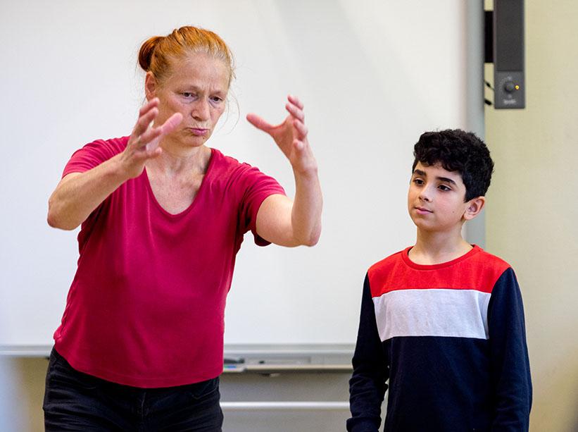 Frau zeigt Jungen eine Übung