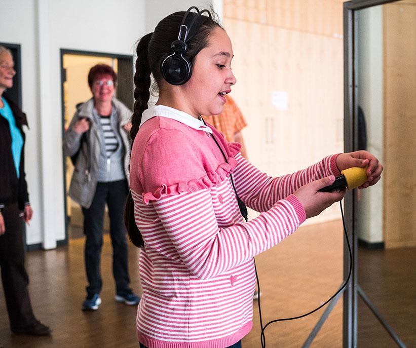 Mädchen mit Aufnahmegerät und Kopfhörern