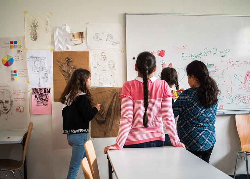 Kinder gucken Zeichnungen an der Wand an