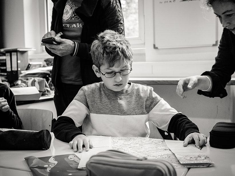 sw-Foto: Junge faltet Plan zusammen