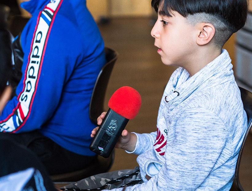 Junge erzählt ins Mikrophon