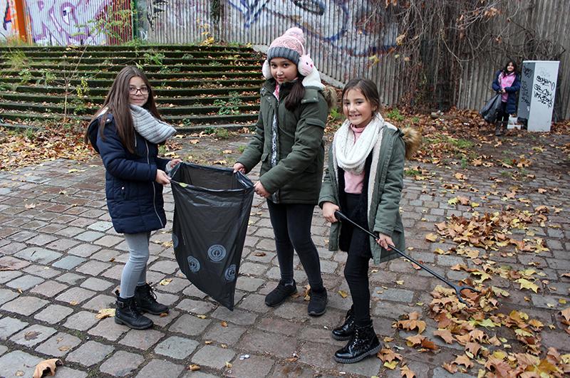 Mädchen sammeln Müll im Kiez