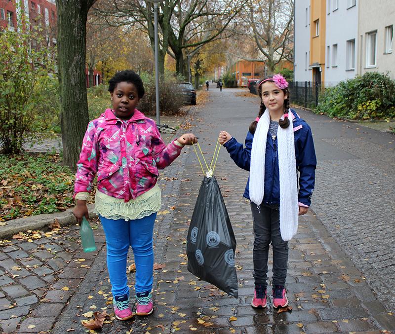 zwei Mädchen mit Müllbeutel