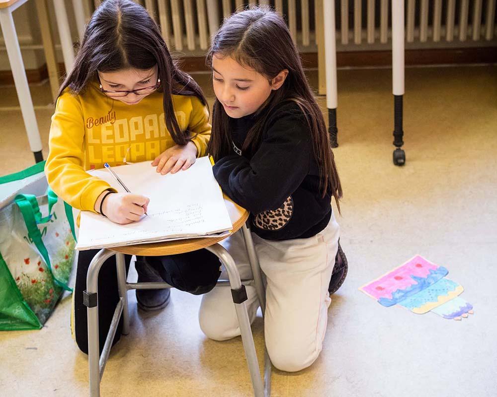 zwei Mädchen schreiben etwas auf