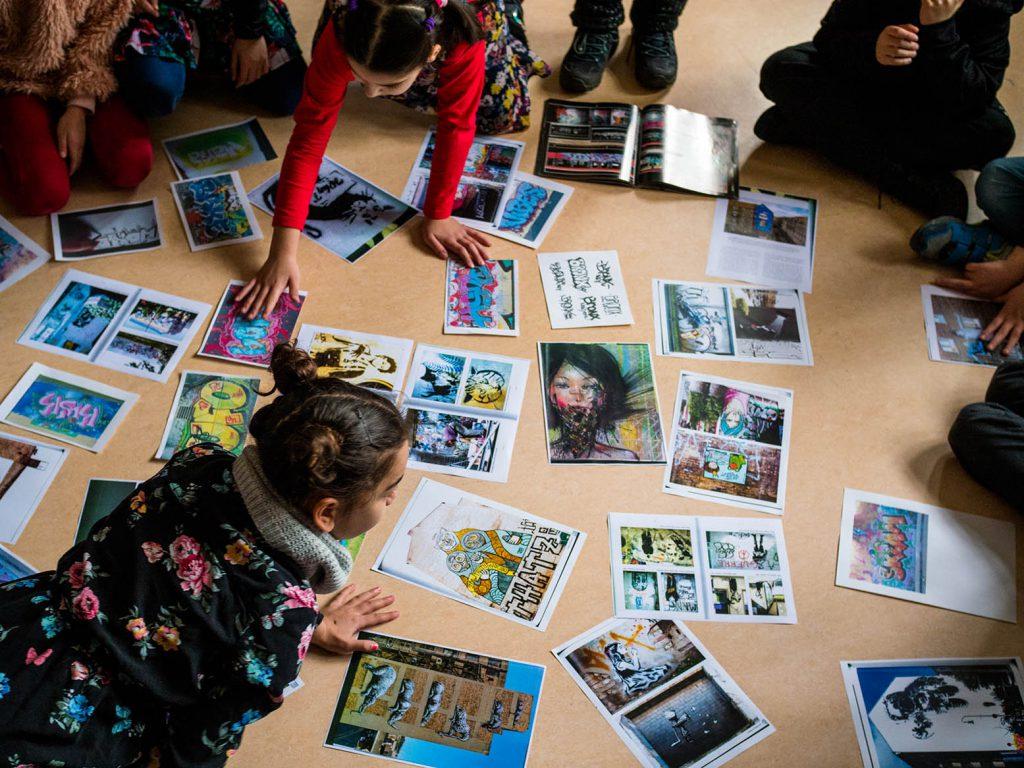 Kinder schauen Bilder an